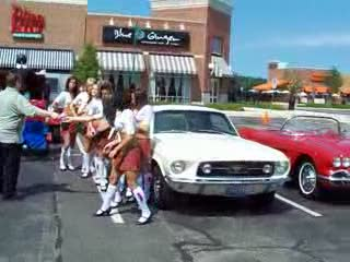 Add Comment To: Tilted Kilt Ladies posing with a classic Mustang