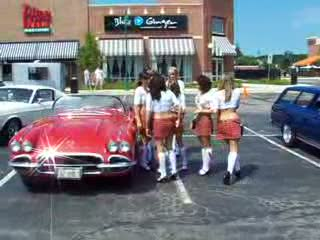 Add Comment To: Tilted Kilt Ladies posing with a classic Corvette